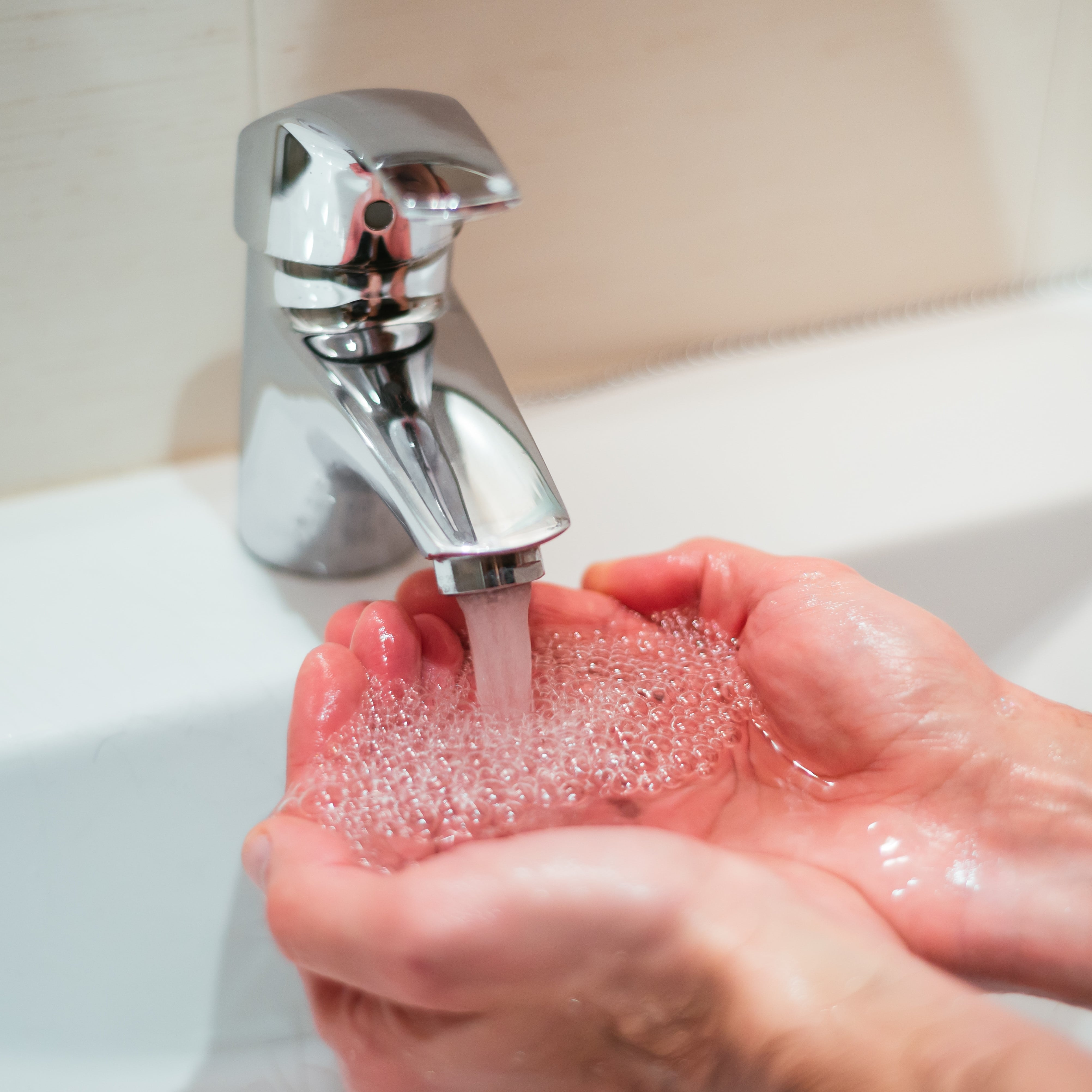 Closeup shot of a person washing hands in the sink